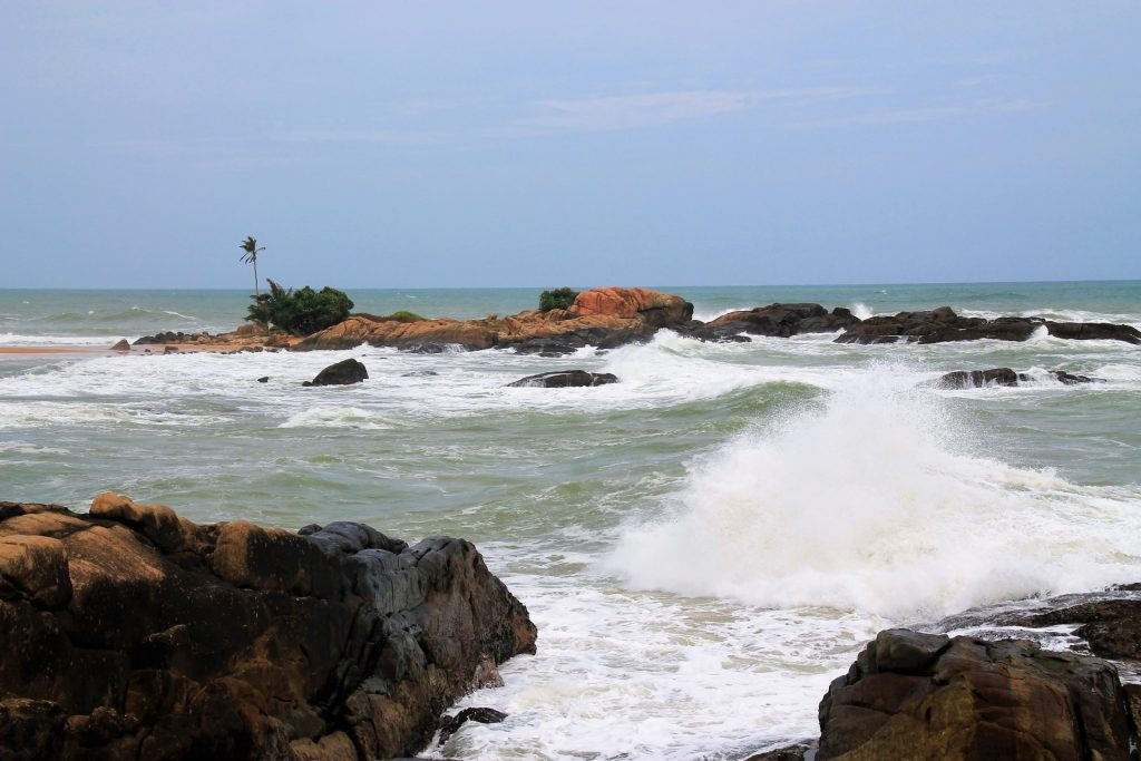 Little island and the stormy sea at Dodanduwa harbour